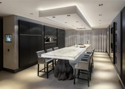 Matt Grey Kitchen Run With Lit Onyx Stone Sculptural Dining Table.