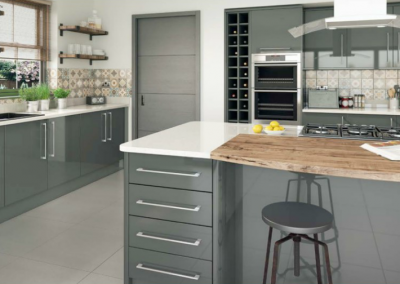 Grey Gloss Vinyl Wrapped Kitchen With Compound Worktops & Finished With Timber.