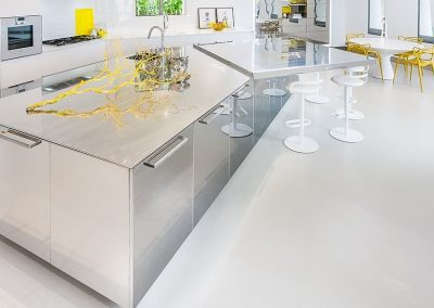 This Polished Steel Kitchen Design was taken to another level here with an extended steel Island worktop formed to create an angled dining breakfast penninsular and bar solution.